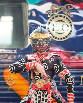 Dancer in a traditional Thai lion mask posing in front of train carriages