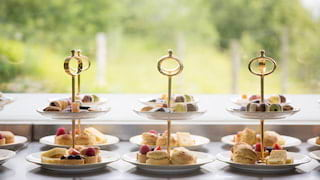 Three cake stands in a row, each laden with scones, cakes and macarons