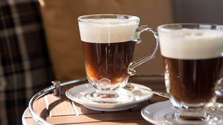 Close-up of two Irish coffees topped with cream, on a circular wooden coffee table