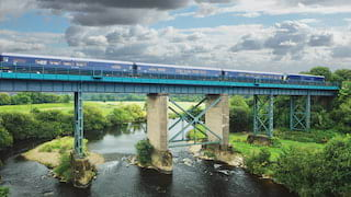 Royal blue train carriages crossing a rail bridge over a river