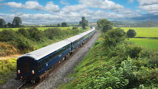 Royal blue train rolling across the lush Irish countryside under blue skies