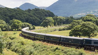 Blue train carriages curving through an Irish valley with mountains either side