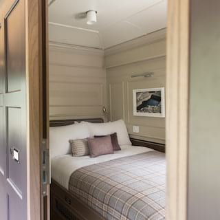 Light and elegant train berth with a double bed and tartan soft furnishings