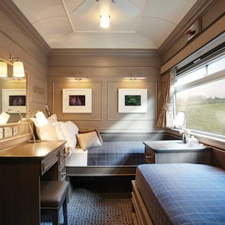 Elegant train twin berth with large picture windows and warm tartan styling