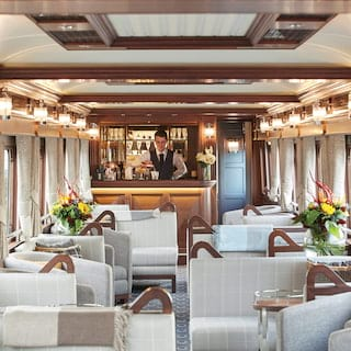 Train bar car with elegant wood-panelled bar area and warm grey soft furnishings