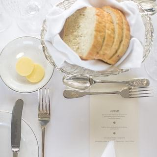 Close-up of a table setting with silverware, menu card and silver bread basket
