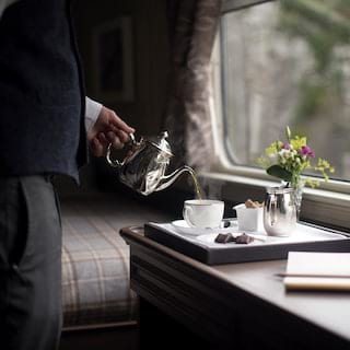 Steward pouring tea from a silver pot into a teacup on a room service tray