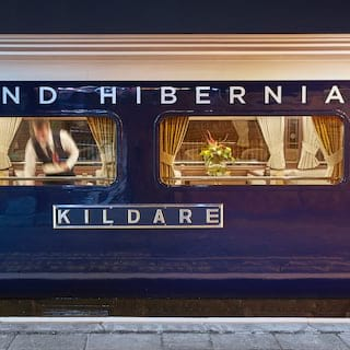 Gleaming royal blue train exterior with 'Grand Hibernian' lettering in silver