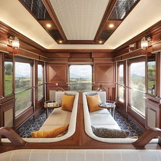 Wood-panelled train observation car with banquette seating and picture windows