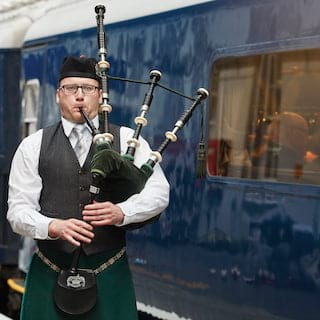 Irish bagpipe player in a kilt playing next to gleaming blue train carriages