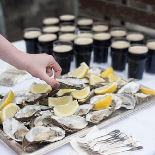 A hand selecting an oyster from an oyster platter served with glasses of guinness