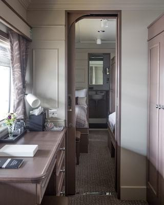 Sunlight-filled interconnecting train cabin with wooden writing desk and wardrobe