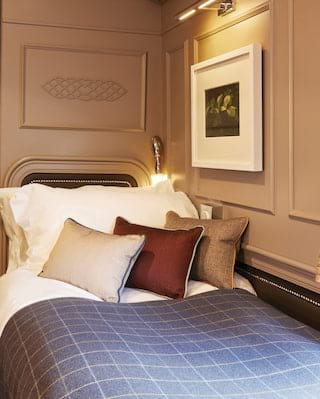 Cosy single berth train cabin decorated with warm plum and cream hues