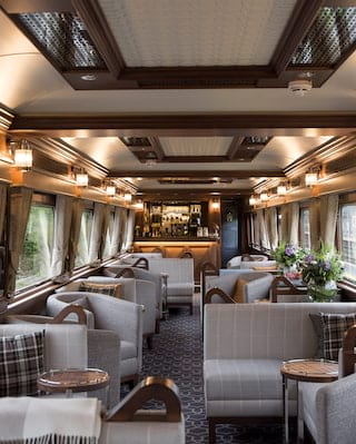 Elegant train bar car in ambient soft light with grey tweed soft-furnishings