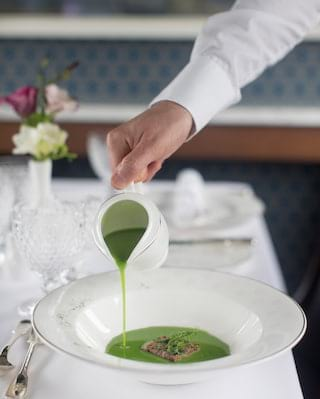 Close-up of pea soup being poured into a large circular white bowl