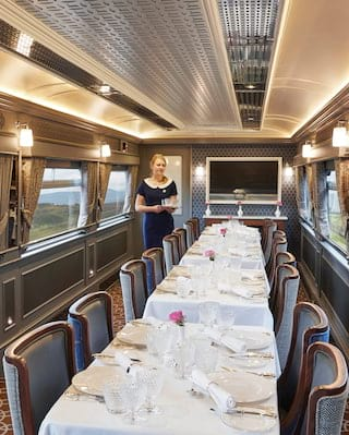Train dining car with elegant wood-panelled walls in grey and tan hues