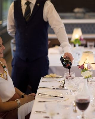 Waiter pouring red wine into a crystal wine glass at a linen-coated table