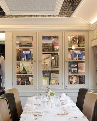 Train dining car containing a glass cabinet library filled with books
