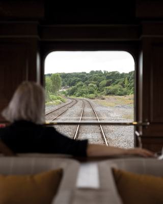 Lady looking through a train window at tracks and scenic countryside beyond