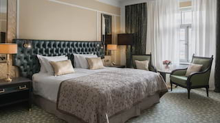 Elegant hotel room with a pillowy king-bed and green-leather headboard