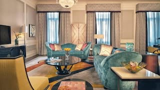 Double-height hotel suite lounge area with teal velvet sofas and a yellow chair