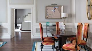Airy avant-garde-style hotel suite with an oval dining table and orange chairs