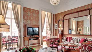 Grand art-nouveau hotel suite with a crystal chandelier and peach-coloured wallpaper
