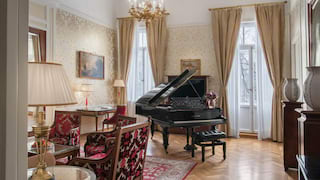 Baby grand piano in an elegant hotel suite with parquet floor and pale gold hues