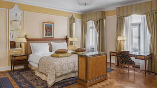 Elegant hotel room with parquet floor art-nouveau chandelier and pale cream hues