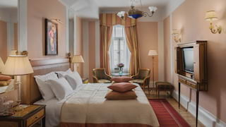 Double-height hotel room with blush pink walls and rosewood furnishings