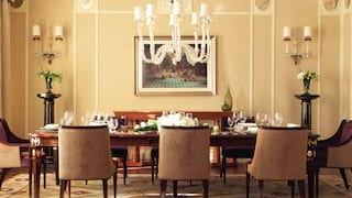 Spacious dining room with a polished wood banquet table under a grand chandelier