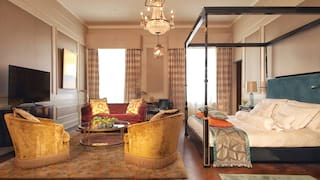 Stylish hotel room with parquet floors, four-poster bed and yellow velvet armchairs