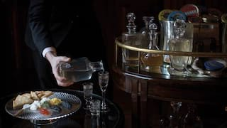 Hand pouring vodka from a glass carafe next to a silver tray of caviar