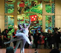 Two graceful ballet dancers and an orchestra performing at L'Europe