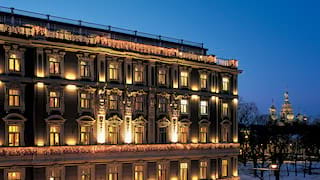 The illuminated facade of an art nouveau hotel against the St Petersburg night skyline