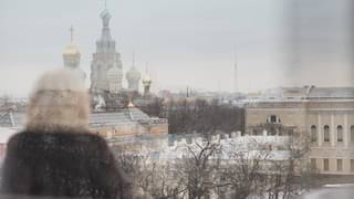 View through a window of a lady gazing across the snowy St Petersburg skyline
