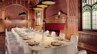 Formal banquet table lit by candelabras in a grand wood-panelled room