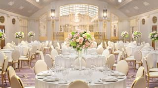 Circular banquet tables set for a wedding in a grand ballroom with lilac tones