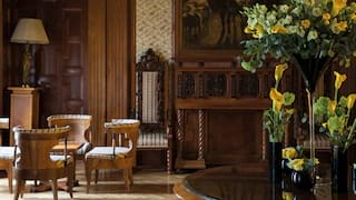 Grand reception room with polished-wood furniture and an ornate floral display