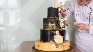 Patissier in chef whites adding icing to a four-tiered black and gold wedding cake