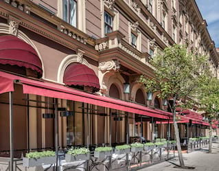 Red arched window awnings lining a sandstone hotel in St Petersburg