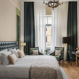 Double-height hotel room with parquet flooring and forest-green soft furnishings