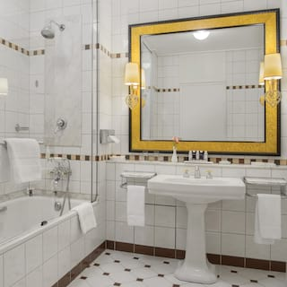 Marble-tiled bathroom with a vast square gold mirror above a porcelain sink