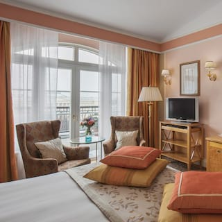Cushions displayed at the end of a bed in an elegant hotel room with terracotta hues