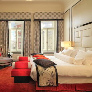 Double-height hotel room with monochrome decor and red accents