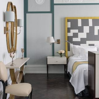 Light and fresh hotel suite with dark polished wood floor and stylish furnishings