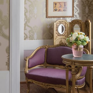 Baroque loveseat with a gold frame and lilac fabric in an ornate hotel room