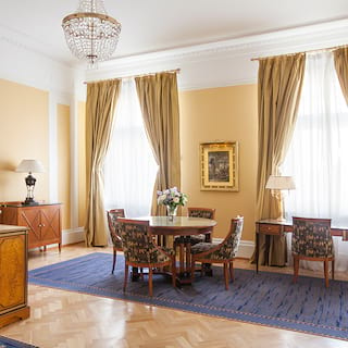 Spacious double-height hotel suite lounge with pale gold wallpaper and parquet floor