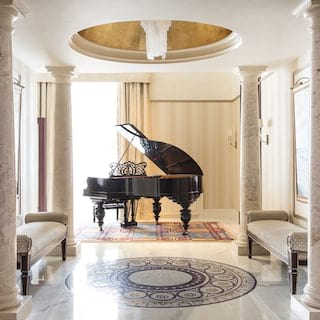 A grand piano at the end of a column-lined hall with a mosaic tiled floor