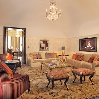 Elegant hotel suite lounge area with art-nouveau furnishings and cherry red accents